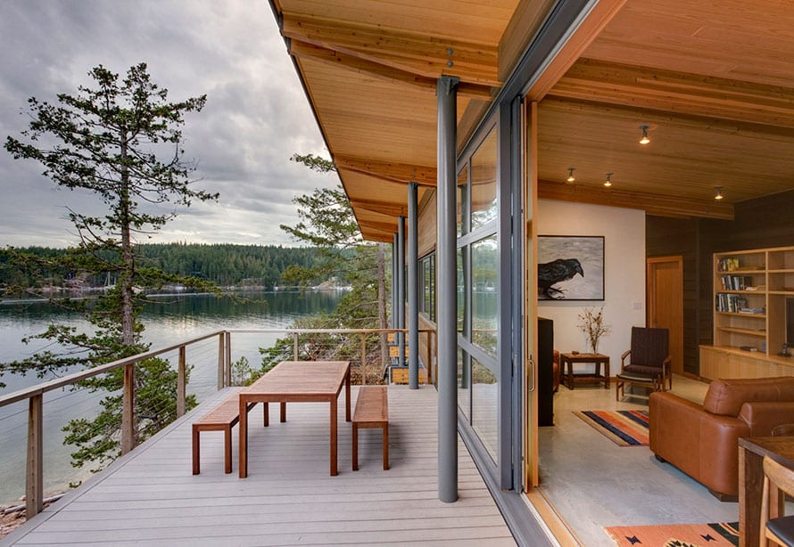 Wood clad lift and slide doors by the sea