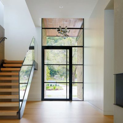 Glass and steel pivot door with sidelites in entryway