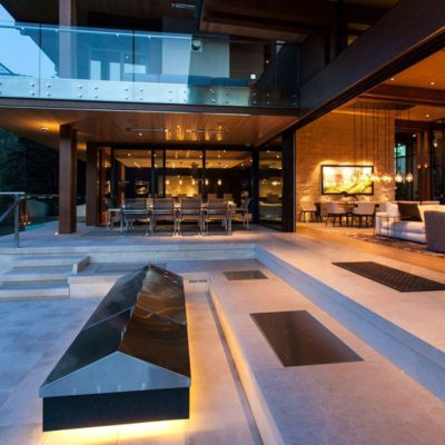steel lift and slide doors open, exterior view looking into dining area at dusk