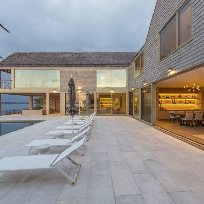 Large multi-panel wood lift and slide doors in home overlooking the sea