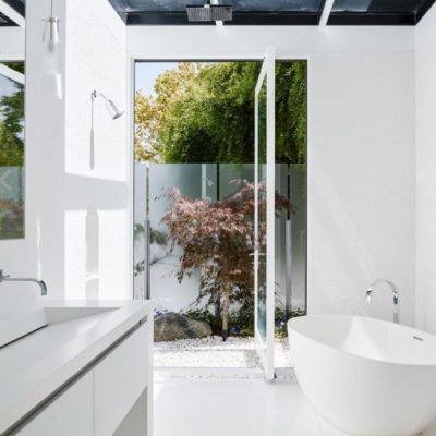 Wood and glass pivot door opening bathroom to outdoors