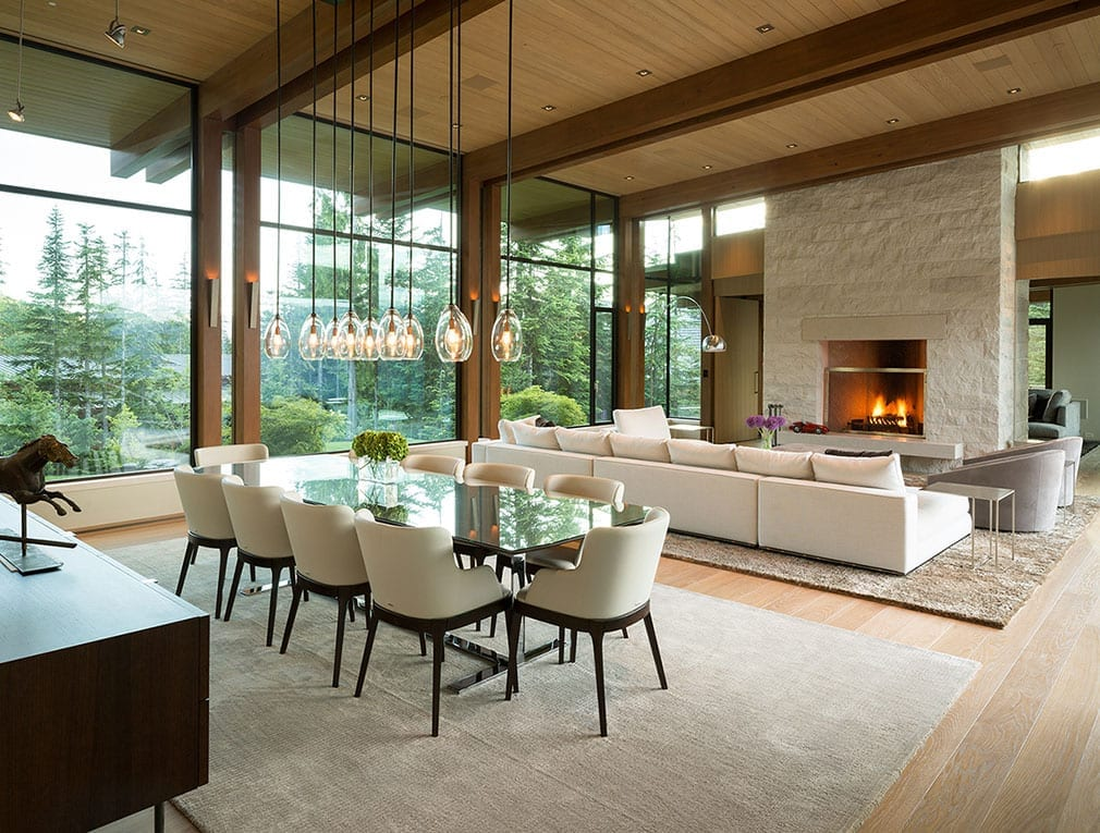Living room table with large massive steel windows in background of modern home