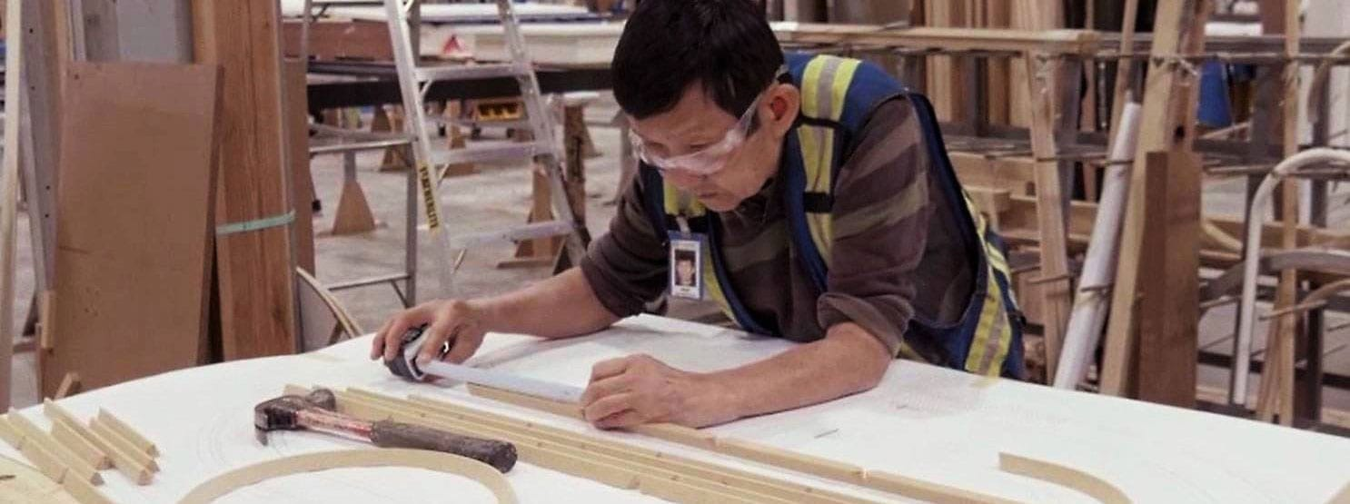 Window factory worker calculating lengths for custom wood windows