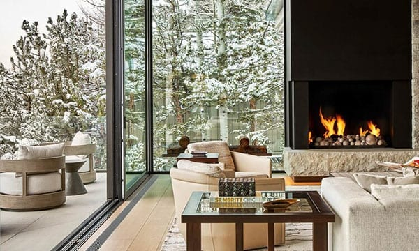 Reynaers Aluminum lift and slide doors with fireplace and snowy exterior visible through glass