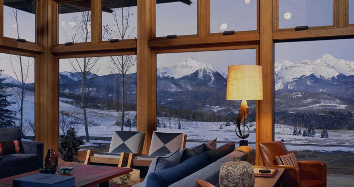 Looking through large custom wooden windows to reveal a beautiful mountain landscape.