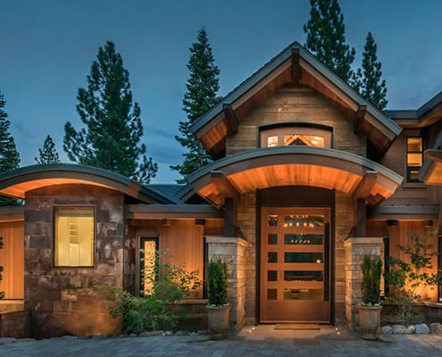 Exterior night view of front entry of modern residence with wood clad windows and doors