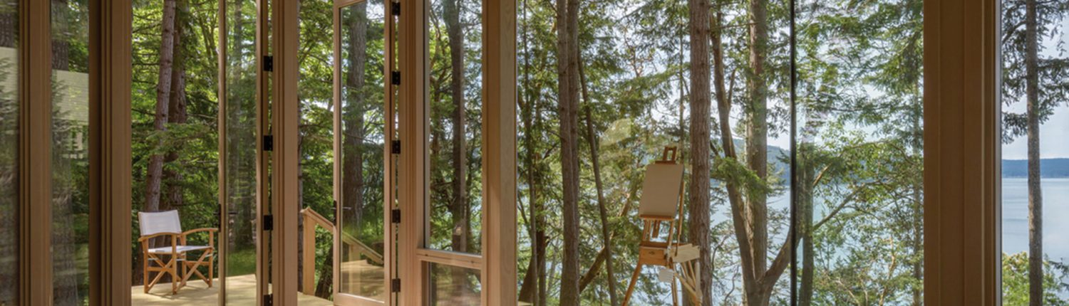 Looking out of a beautiful modern mountain home with floor to ceiling custom glass windows.
